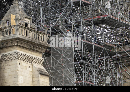 PARIS, FRANCE - 19 APRIL 2019 Notre Dame cathedral, a man positions sandbags along the edge of the walls. The remains of the melted scaffolding behind - Stock Image