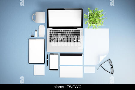 top view of blue desktop with devices, branding elements and office stuff 3d rendering mockup - Stock Image