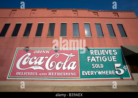 A vintage Coca Cola sign painted on the side of a building in downtown Rogers, Arkansas, U.S.A. - Stock Image