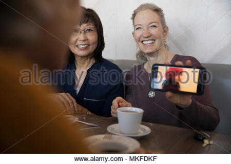 Proud senior woman with camera phone showing photograph of granddaughter to friends - Stock Image