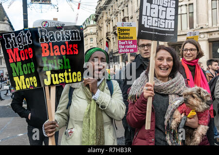 London, UK. 9th Dec, 2018. A woman carries a placard 'Figth Racism - More Blacks, More Irish, More Justice' in the united counter demonstration by anti-fascists in opposition to Tommy Robinson's fascist pro-Brexit march. The march which included both remain and leave supporting anti-fascists gathered at the BBC to to to a rally at Downing St. Police had issued conditions on both events designed to keep the two groups well apart. Credit: Peter Marshall/Alamy Live News - Stock Image