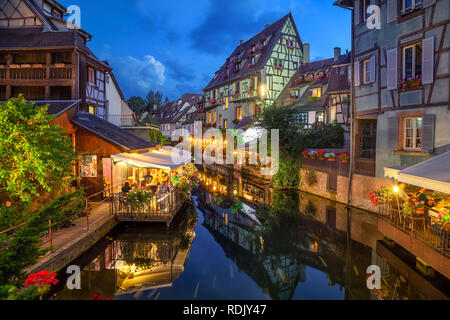 Colmar, France. Half-timbered houses and verandas of restaurants reflecting in the water at dusk in Petite Venise area - Stock Image