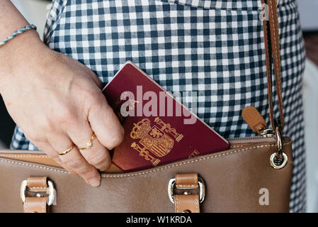 Close up photo of stylish woman taking Spanish passport out the purse. - Stock Image