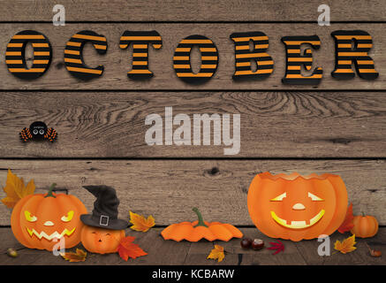 funny halloween pumpkins with light on wooden background with letters october - Stock Image