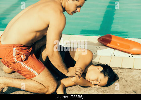 Lifeguard positioning accident woman during rescue procedure training. Toned image. - Stock Image