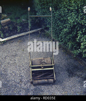 1960s, a small, old rusty hand-operated lawn mower on garden path. - Stock Image