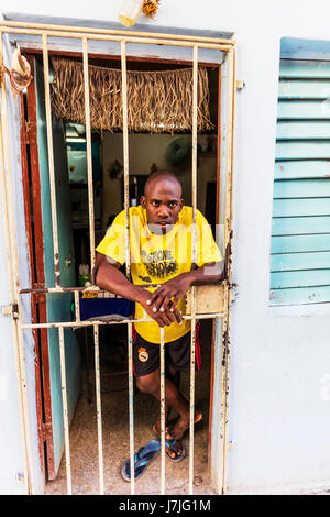 Young Afro Cuban man looking out from his home in Havana Cuba, poverty in Cuba, Cuban poverty, poor Cuban man, Cuban - Stock Image