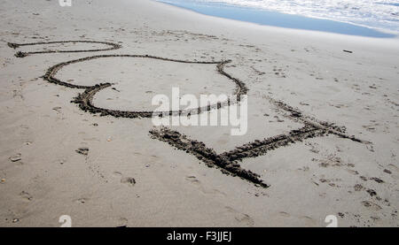 I 'heart' u written in the sand on a beach in France. A wave breaks in the top right hand corner.  The heart - Stock Image