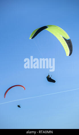 Two paragliders fly paraglides in the blue sky. - Stock Image