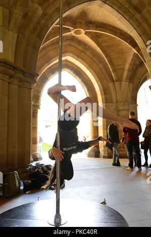 Glasgow, UK. 12th, September, 2018. Glasgow, Scotland, UK. A young lady demonstrates pole dancing moves on behalf on a pole dancing club during Freshers Week in the cloisters at Glasgow university. - Stock Image