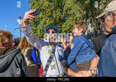 London, UK. 20th October 2018. 'Elvis' who has arrived to play opposite Downing St takes a selfie with marchers at the end of the People's Vote March calling for a vote to give the final say on the Brexit deal or failure to get a deal. They say the new evidence which has come out since the referendum makes it essential to get a new mandate from the people to leave the EU. With so many on the march the crowding meant many failed to reach Parliament Square and came to a halt in Whitehall. Peter Marshall/Alamy Live News - Stock Image