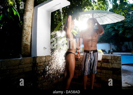 A couple showering poolside. - Stock Image