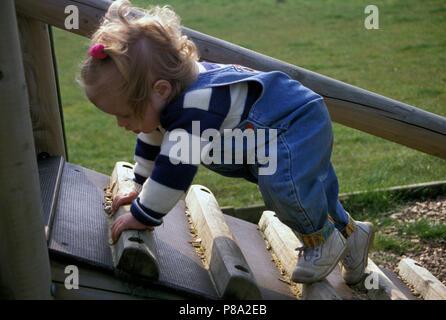 agile toddler climbing apparatus in playground - Stock Image