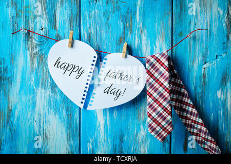 the text happy fathers day written in two notepad pages forming a heart hung with clothespins in a clothes line next to a necktie, against a rustic bl - Stock Image