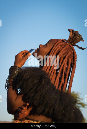 Himba tribe young woman looking at a drone in the sky, Cunene Province, Oncocua, Angola - Stock Image