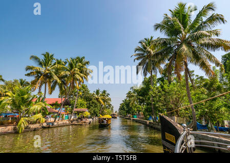 Horizontal view of traditional riceboats sailing down a canal in Kerala, India. - Stock Image