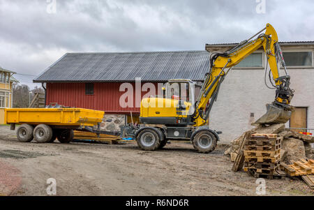 FLODA, SWEDEN - NOVEMBER 21 2018: Medium sized yellow excavator with trailer resting it's bucket on pile of wood pallets - Stock Image