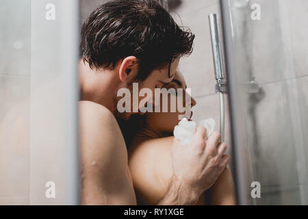 naked man and attractive woman hugging and taking shower with loofah - Stock Image
