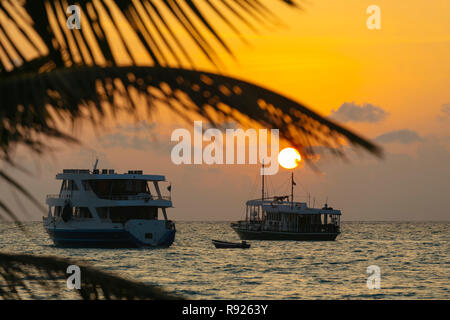 Tranquil scene with view of ships in sea at sunset, Thulusdhoo, Male, Maldives - Stock Image