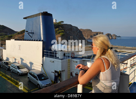 young woman smoking cigarette on ferryboat, Limnos Island, Greece - Stock Image
