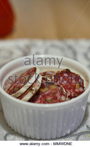 Cut Italian salami pieces in a white bowl - Stock Image