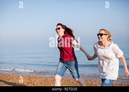 Affectionate lesbian couple holding hands on sunny beach - Stock Image