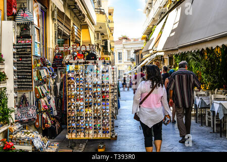 Tourists walk the narrow path between souvenir shops and outdoor vendors selling gifts in the touristic Plaka section of Athens, Greece. - Stock Image