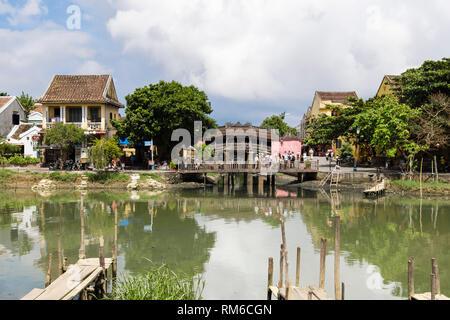 View across Thu Bon River to old Chua Cau or Japanese Covered bridge or Pagoda bridge from An Hoi island. Hoi An, Quảng Nam Province, Vietnam, Asia - Stock Image