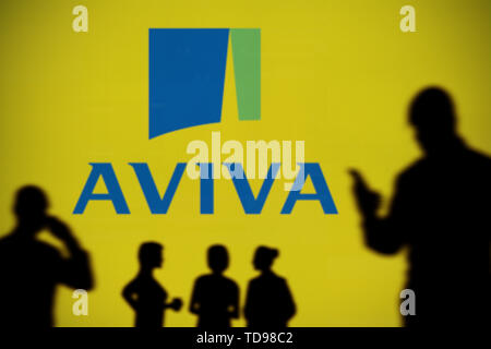 The Aviva Insurance logo is seen on an LED screen in the background while a silhouetted person uses a smartphone in the foreground (Editorial use only - Stock Image