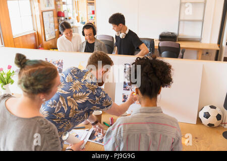Creative designers reviewing story board in office - Stock Image