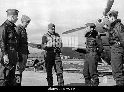 Photo of four young officers of the Fliegertruppe (air force troop) of the Condor Legion in conversation with a captain (middle) in front of a German fighter aircraft of the type Messerschmitt Bf 109 B , at an airfield in Spain. Here, the muzzle of the machine gun in the hollow propeller nose. - Stock Image