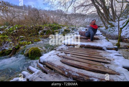 Middle age male tourist ignores warning and slips and fall on icy boardwalk, injuring his head - Stock Image
