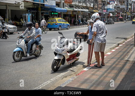 Man with crutches about to ride on a motorcycle. Thailand Southeast Asia - Stock Image