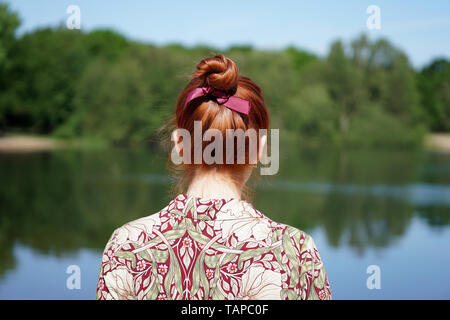 back view of unrecognizable young woman with floral dress and red hair bun looking at lake in solitude - Stock Image