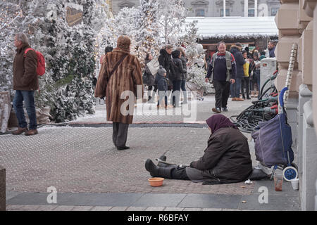 Older lady begging passerby in city square where celebrations of Advent Market happen.  Walkers mostly ignoring plea for help - Stock Image