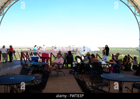 Visitors rest at a sitting area on the elevated walkway over various animal habitats at The Wild Animal Sanctuary. - Stock Image