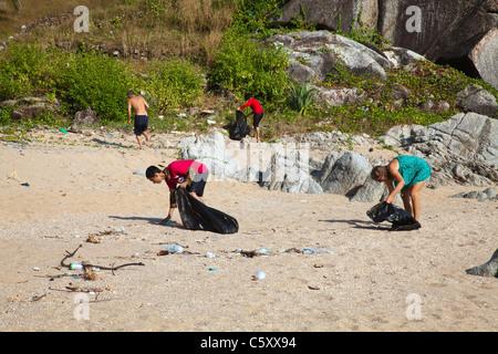Thai schoolchildren schoolclass and volunteers cleaning Paradise Beach. - Stock Image