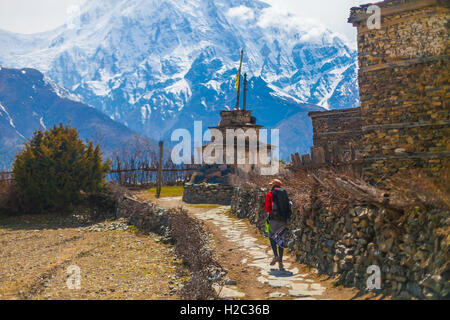 Young Pretty Woman Wearing Red Jacket Backpack Trail Mountains.Mountain Trekking Rocks Path Village. Snow Landscape - Stock Image