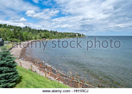 A man loads firewood into a pickup truck in Tofte, Minnesota with the North Shore Commercial Fishing Museum visible - Stock Image