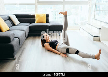 Adult Woman Training ABS Abdominals Doing Scissors With Legs - Stock Image