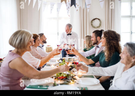 A big family sitting at a table on a indoor birthday party, clinking glasses. - Stock Image