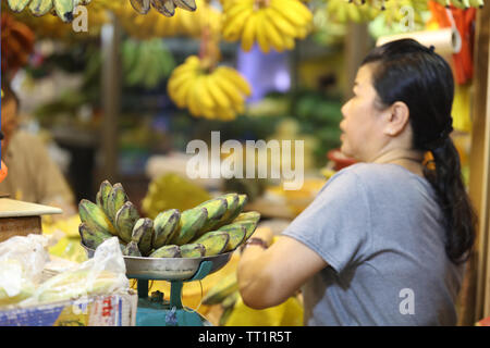 Market seller weighing a type of bananas on a scale in the Indoor market Little India, Singapore on a Saturday morning. - Stock Image