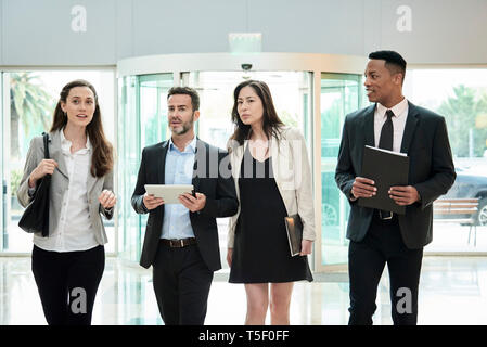 Business people discussing while walking in hotel lobby - Stock Image