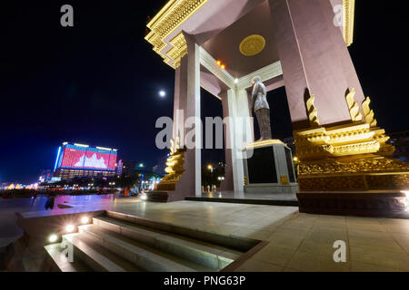 Statue of King Norodom Sihanouk in park with Cambodian flag projected by neon light in the background. In Preach Suramit Boulevard in Phnom Penh, Camb - Stock Image