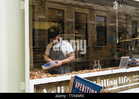 Chef adding topping to pizzas at Aromi cafe Benet Street Cambridge 2019 - Stock Image