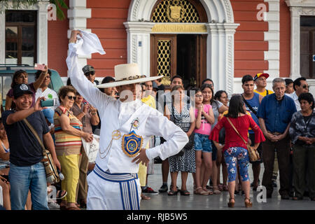 Crowds watching he famous Marinera dance of Trujillo, Peru, in the colonial style main square of the city. - Stock Image