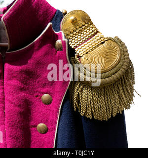 Details of a historic uniform of a French army of the Napoleon wars era. Closeup view of an epaulette. Isolated against the white background - Stock Image