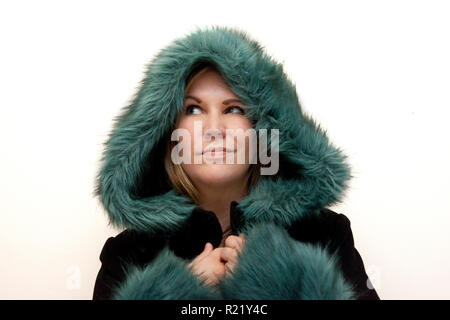 Cheeky smiling model in a beautiful green and black coat ready for winter and happy - Stock Image