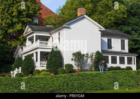 JONESBOROUGH, TN, USA-9/29/18: A homeowner in Jonesborough works on the lawn of an elegant, old home. - Stock Image