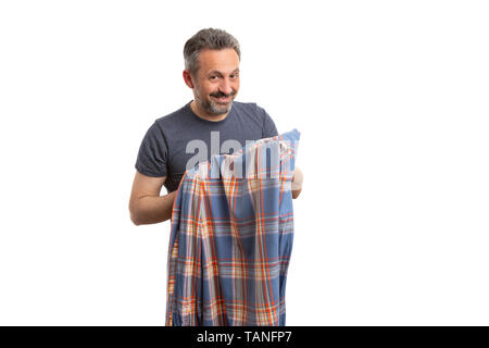 Friendly man holding orange and blue plaid shirt in hand smiling as casual fashion concept isolated on white - Stock Image